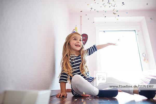 Glückliches Mädchen sitzt auf dem Boden und spielt mit Konfetti