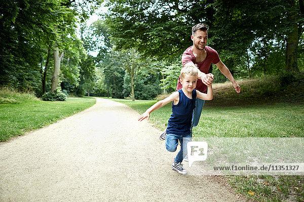 Vater und Sohn rennen im Park