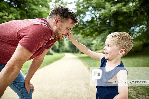 Fröhlicher Junge zwickt Vaters Nase