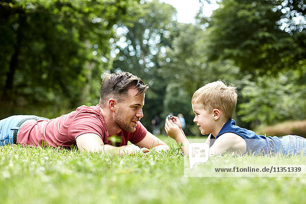Father and son lying in meadow with cell phone