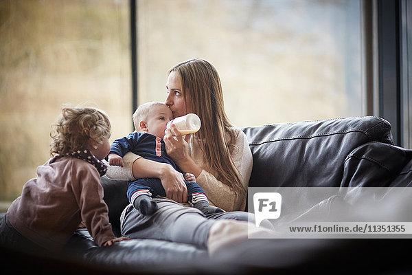 Mutter gibt ihrem Baby das Fläschchen auf der Couch beobachtet von der Tochter