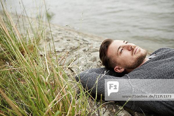 Mann liegt am Flussufer