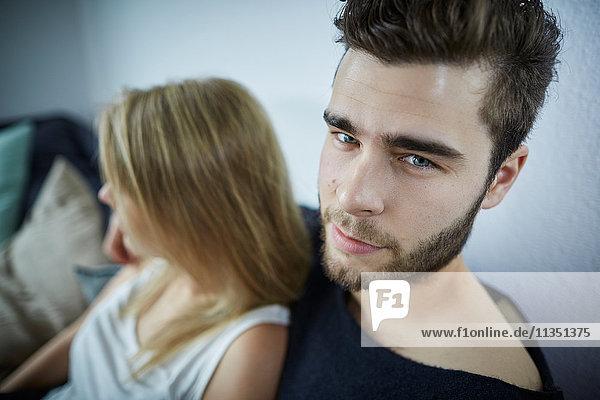 Portrait eines jungen Mannes mit Freundin auf der Couch