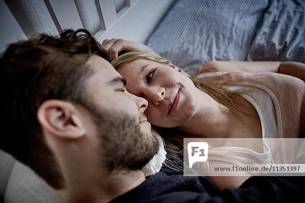 Junges Paar liegt im Bett und schaut sich an