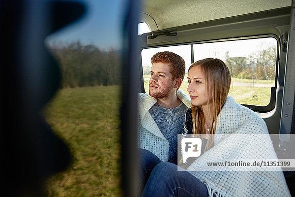 Junges Paar in einem Auto in eine Decke gewickelt