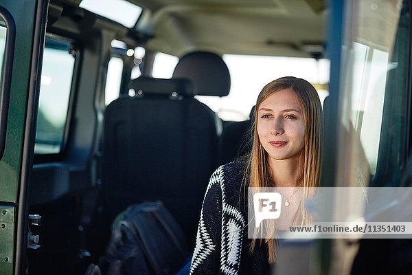 Junge Frau in einem Auto in eine Decke gewickelt