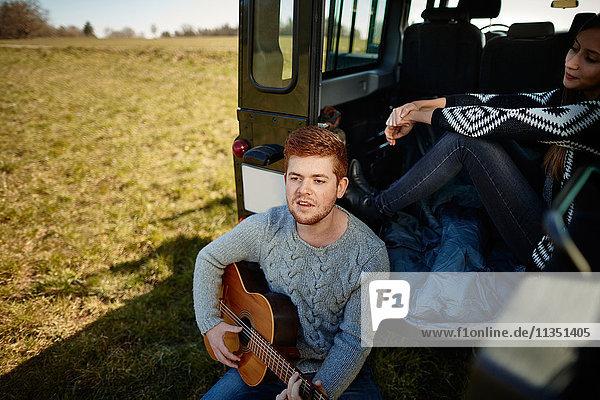 Junges Paar mit Geländewagen auf einer Wiese macht Musik
