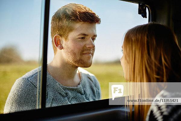 Junger Mann schaut auf Frau hinter Autofensterscheibe