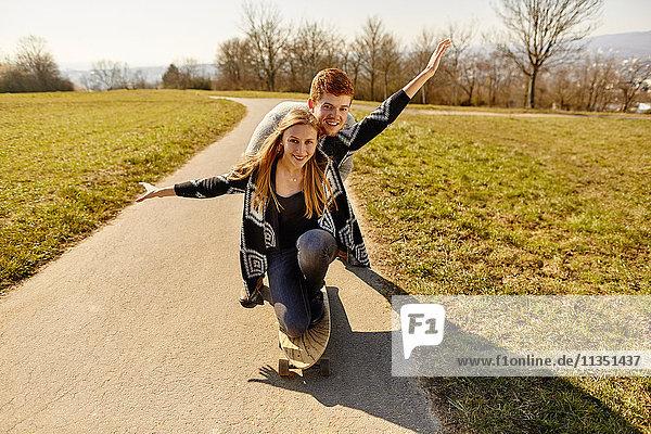 Junges Paar mit Skateboard auf einem Feldweg