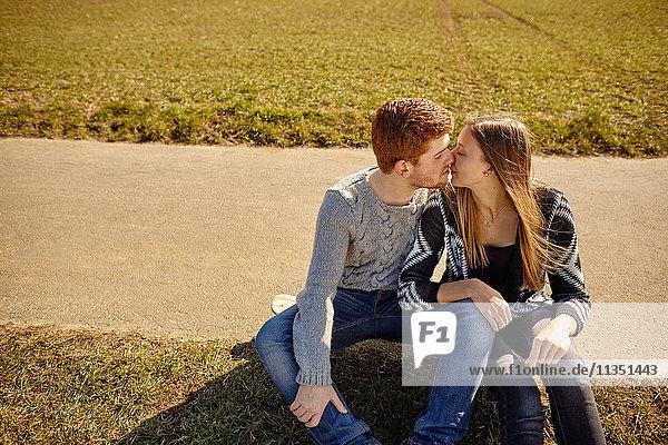 Junges Paar sitzt an einem Feldweg und küsst sich