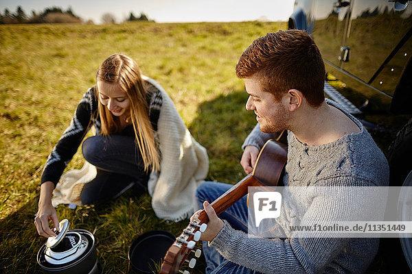Junges Paar sitzt auf einer Wiese neben einem Auto und einem Campingkocher und macht Musik