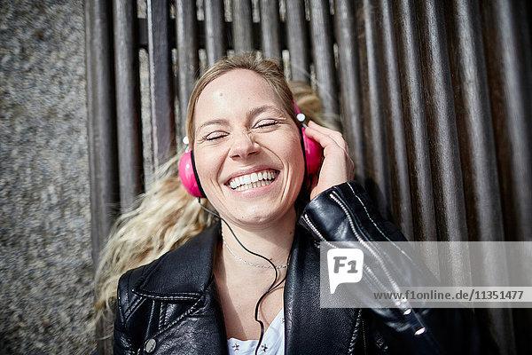 Glückliche Frau mit Kopfhörern liegt auf einer Bank