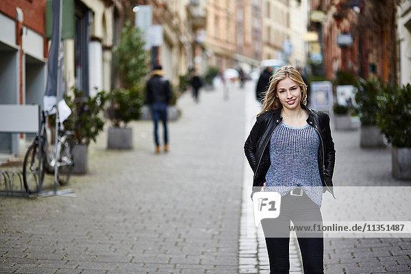 Portrait einer lächelnden jungen Frau in der Fußgängerzone