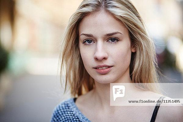 Portrait einer blonden jungen Frau im Freien