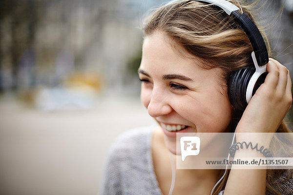 Lächelnde junge Frau mit Kopfhörern