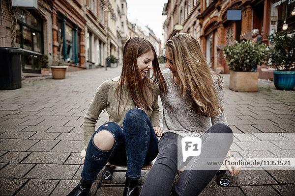 Zwei fröhliche junge Frauen sitzen auf einem Skateboard in der Stadt