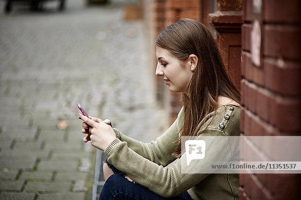 Junge Frau sitzt auf der Türschwelle und schaut auf ihr Handy