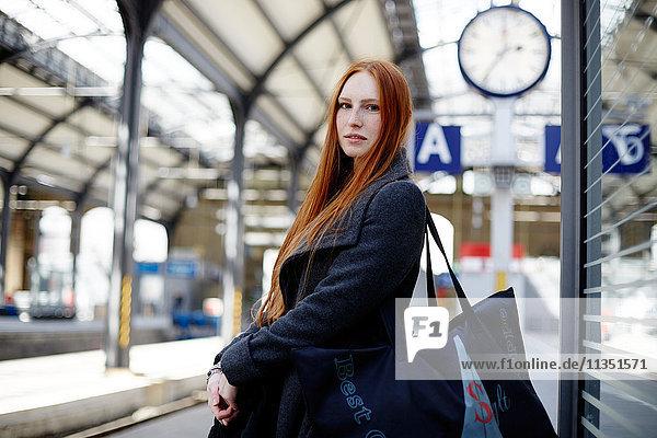 Rothaarige junge Frau auf dem Bahnsteig