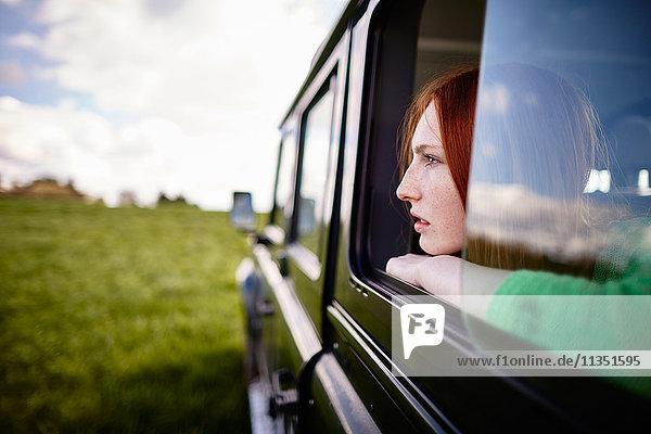 Junge Frau schaut aus dem Autofenster