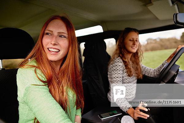 Zwei glückliche junge Frauen auf einer Autoreise