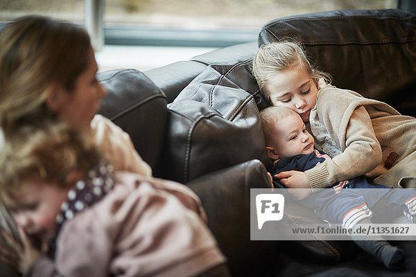 Mädchen und Baby auf der Couch mit Mutter und Tochter im Vordergrund