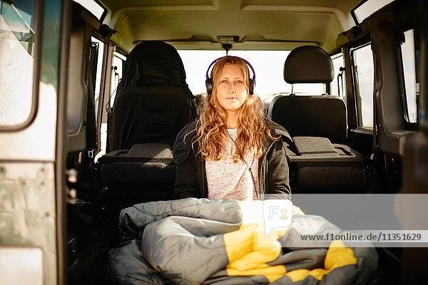 Junge Frau mit Schlafsack und Kopfhörern in einem Geländewagen