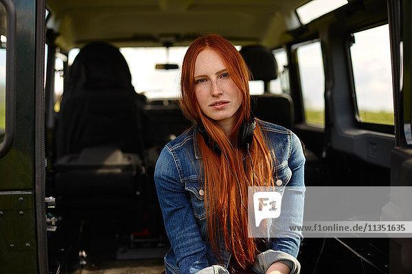 Portrait einer jungen Frau mit Kopfhörern im Auto