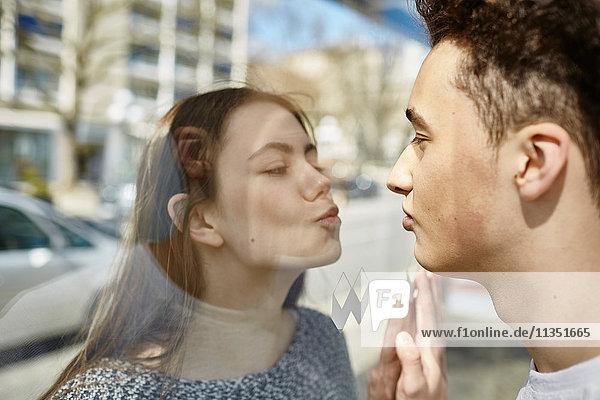 Teenagerpaar küsst sich durch eine Glasscheibe hindurch