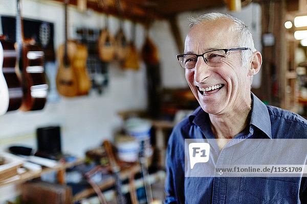 Laughing guitar maker in his workshop