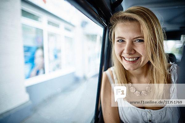 Portrait einer lächelnden jungen Frau in einem Auto