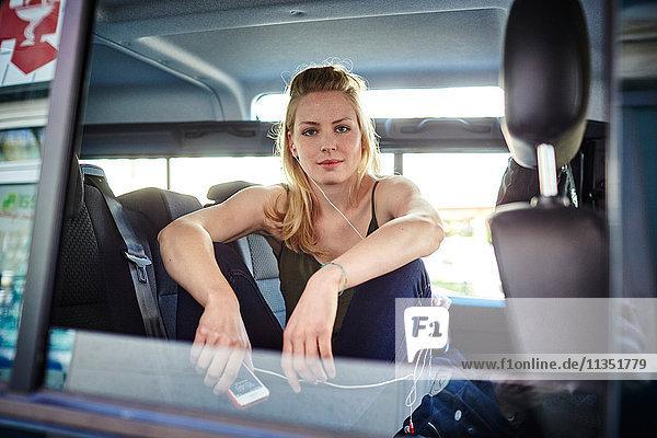 Junge Frau im Auto mit Ohrhörer und Handy