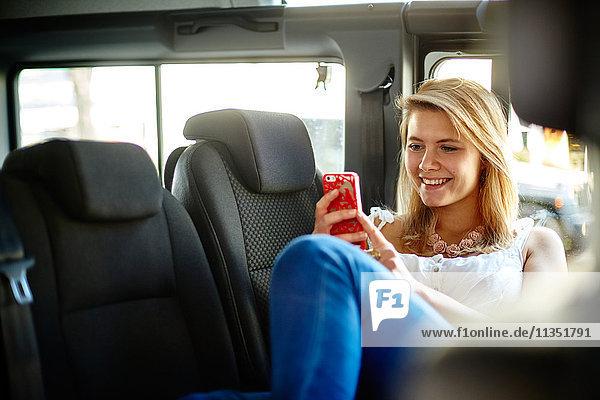 Lächelnde junge Frau im Auto schaut auf ihr Handy