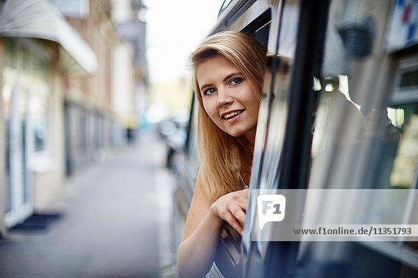 Junge Frau im Auto schaut aus dem Fenster