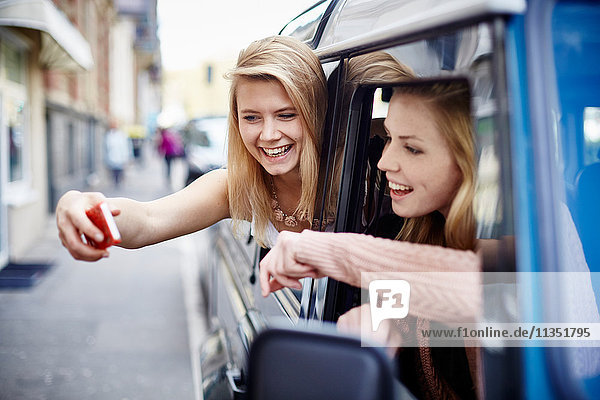 Two happy young women leaning out of car window taking a selfie