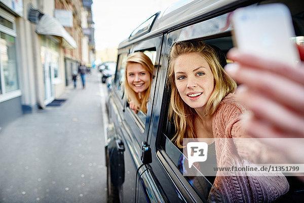 Zwei fröhliche junge Frauen lehnen sich aus dem Autofenster und machen ein Selfie