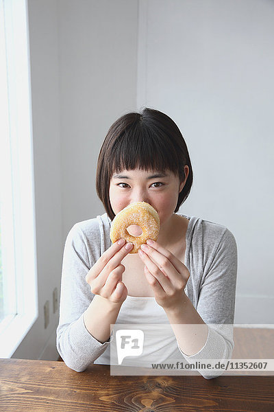 Young Japanese woman eating donut in airy room