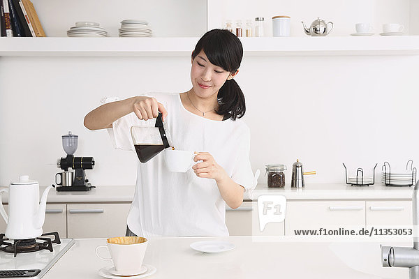Young Japanese woman preparing coffee in the kitchen
