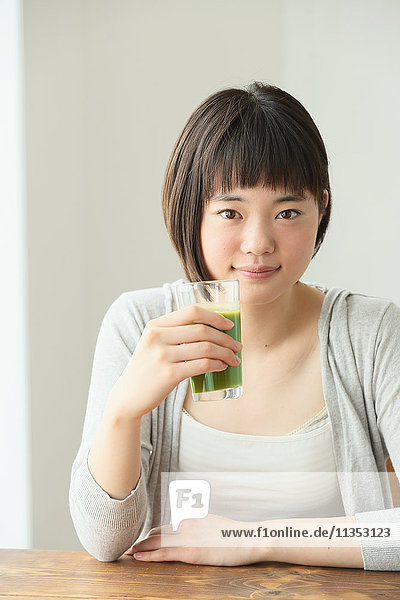 Young Japanese woman drinking in airy room