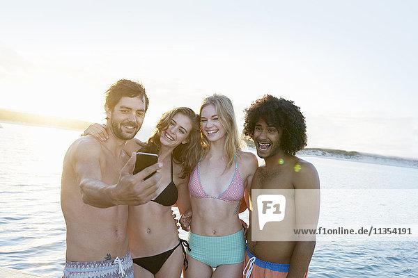 Junge erwachsene Freunde in Bikinis und Badehosen  die sich bei Sonnenuntergang im Sommer selbst tragen.