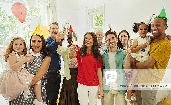 Portrait begeisterte multiethnische Mehrgenerationen-Familie feiert Party mit Champagner und Partyhüten