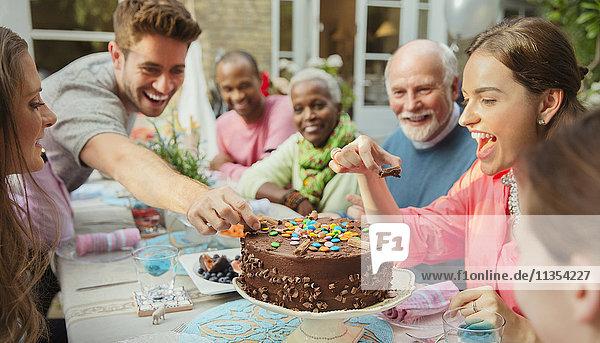 Familie greift nach Bonbons auf Schokoladen-Geburtstagskuchen am Terrassentisch