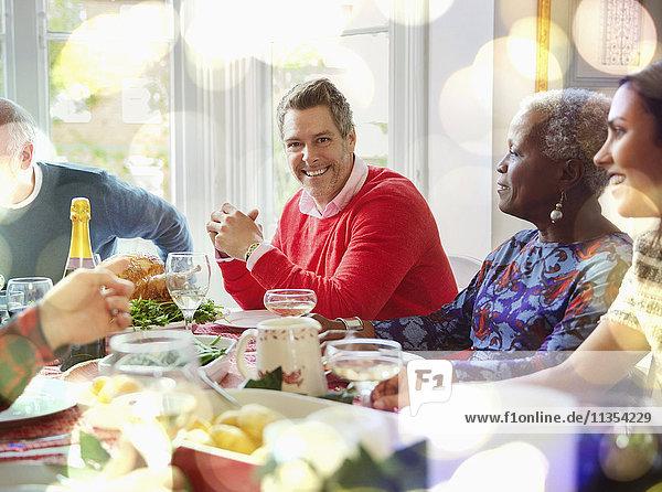 Portrait lächelnder Mann beim Weihnachtsessen am Tisch