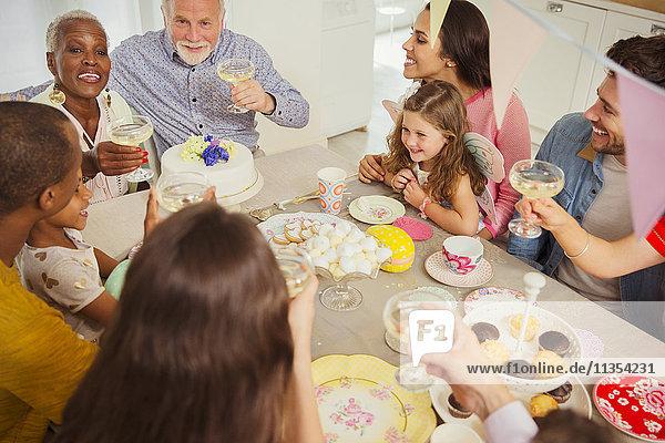 Multiethnische Mehrgenerationen-Familientoast mit Champagner am Tisch