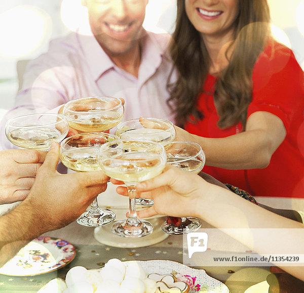 Lächelndes Paar  das mit Freunden am Tisch auf Champagnergläser anstößt.