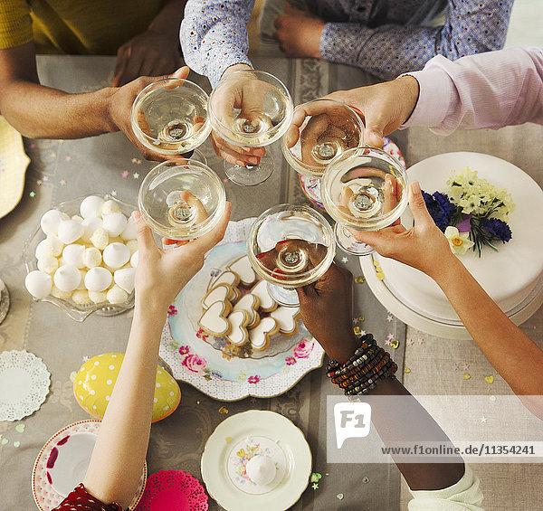 Overhead-Ansicht Freunde toasten Champagnergläser über Ostern Desserts