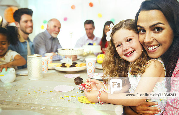 Portrait smiling mother and daughter hugging at birthday party table
