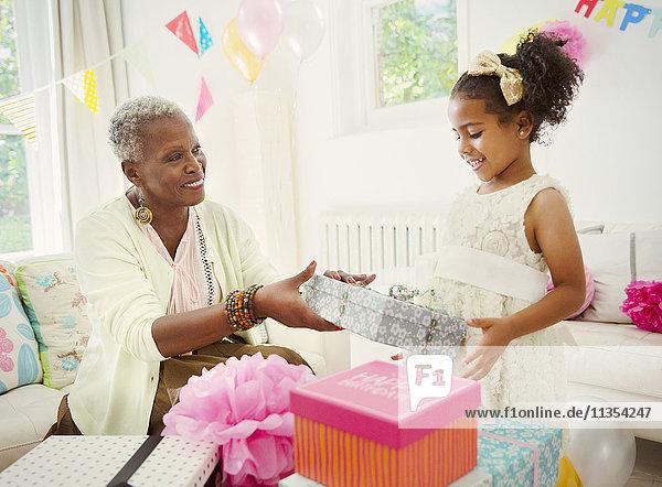 Mädchen schenkt Großmutter Geburtstagsgeschenk auf der Party