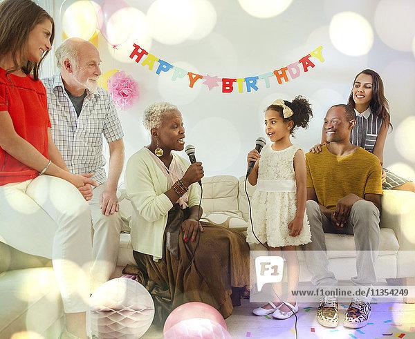 Großmutter und Enkelin singen Karaoke mit Mikrofonen auf der Geburtstagsfeier
