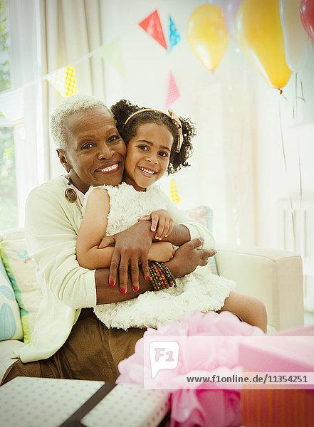 Portrait lächelnde Großmutter und Enkelin umarmend auf der Geburtstagsfeier