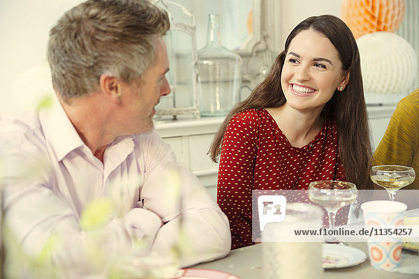 Lächelndes Paar beim Reden und Champagnertrinken am Partytisch